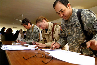 Army Major Darrin Frye (right) reviewed exams last month taken by military personnel in Iraq. In 2006, the Army had to promote more officers ahead of its own timetables.