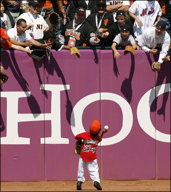 Manny Jr. tosses a baseball to fans during American League batting practice.