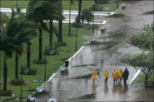 People walk in the rain at a park in Kingston, Jamaica, as Hurricane Dean neared the island Sunday.