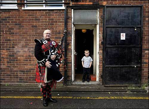 Piper Bob Porteous, who served in the Scots Guards in 1948, prepared to warm up in East London, as 4-year-old Terry Abbott watched.