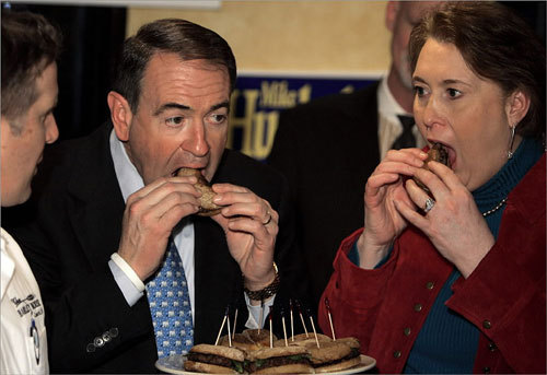 Republican presidential candidate Mike Huckabee (center) and his wife Janet try the newly-created 'Huckaburger', made by the Bayley House restaurant in Concord, N.H.