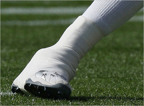 Tom Brady stretched his taped foot at Patriots practice.