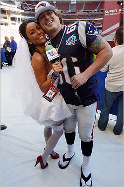Patriots long snapper Lonnie Paxton gets a hug from Mexican television reporter Ines Gomez Mont. Gomez wore the dress to propose to Tom Brady, to which the Pats QB responded, 'I'm a one woman man.'
