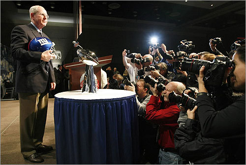 Surrounded by cameras, Tom Coughlin posed next to the Lombardi Trophy.