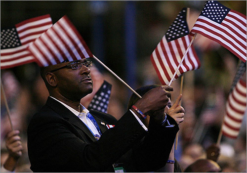A delegate waved US flags while listening to former US President Bill Clinton address the 2008 Democratic National Convention.