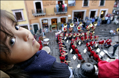 Mariana Vanegas, 3, watches a band performance at the Plaza Gitia in the city of Zacatecas.