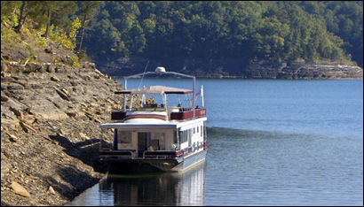 Tied up in a cove on Cumberland Lake, a houseboat of vacationers is a common -- and populat -- sight in Kentucky.