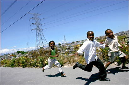 Children play beneath power lines in Khayelitsha, a township established in 1984 to house black families forced out of Cape Town.