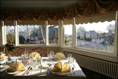 The dining area at Lighthouse Inn Resort and the rooms in the mansion are full of sunlight and have views of Long Island Sound. The front of the inn looks down a road leading to the water.