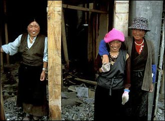 Three Tibetan construction workers pose in Kandze. These women carry large loads of rock and dirt for very little money every day.
