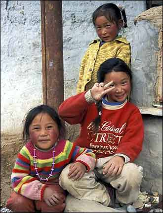 Three Tibetan girls hamming it up for the camera. The smiles come easily for the children.
