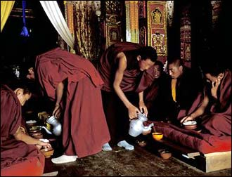 A group of monks take a break to enjoy some Tibetan tea (butter, black tea, salt).