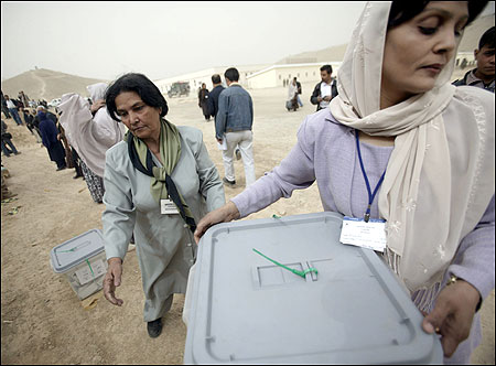Workers at the United Nations Election Counting Center passed along ballot boxes yesterday in Kabul, the day after the first democratic presidential election in Afghanistan.