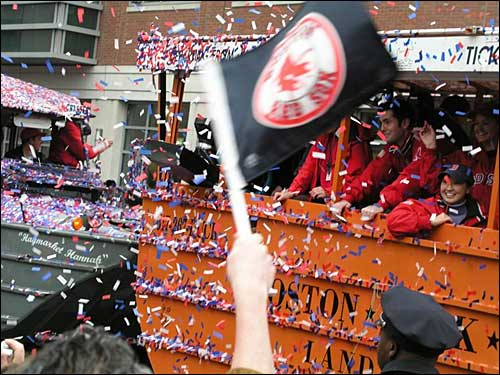 A fan waves a Red Sox flag as confetti rains down on the parade in this photo by Kevin Murphy of Billerica.