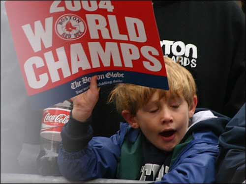 A young fan waves a '2004 World Champions' sign at the front of the parade crowd.