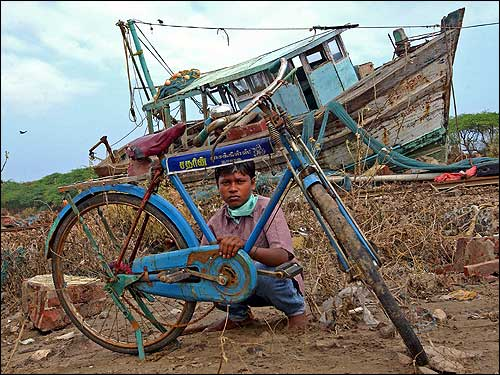 A child repairs a bicycle that was carried away by the tsunami.