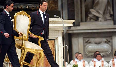 The pope's chair was carried during Mass yesterday at St. Peter's Basilica in Rome. John Paul II did not take part in the Mass because of his frail health.