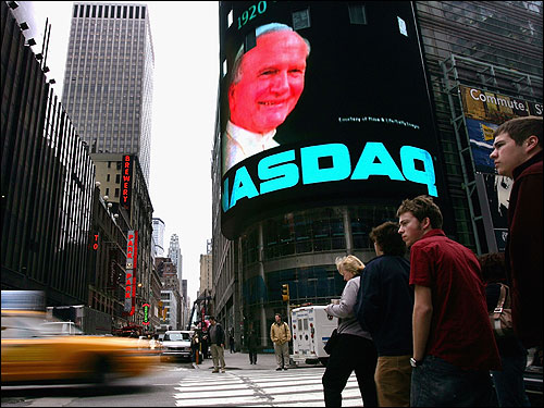 Pedestrians walked past a video screen image of Pope John Paul II in Times Square Friday. New Yorkers mourned the passing of the pope in a variety of ways, including graffiti murals, Masses, and video tributes.
