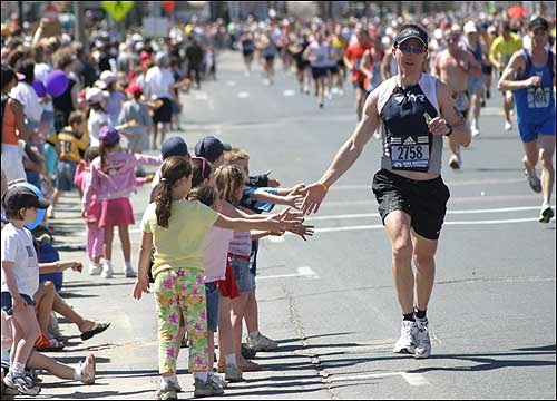 Young fans held their hands out for a low-five from a marathon runner.
