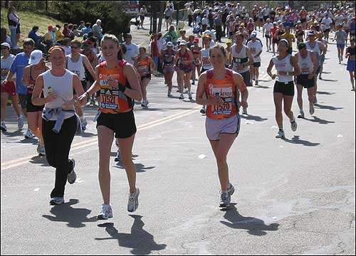 Sisters Noel (in orange on left) and Lyndsey Erickson (in orange on right) ran their first marathon together to raise money in honor of their father for the Dana Farber Cancer Team. They were all smiles as they ran up Heartbreak Hill.