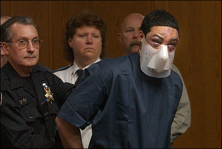 Esteban Carpio was led into court yesterday wearing what officials described as a ''spit shield'' intended to protect others from blood and other fluids. Providence police say Carpio was injured when he jumped out a window and in a struggle with police. Relatives allege police brutality.