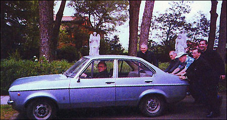 Priests pushed the car in hte pope's garden.