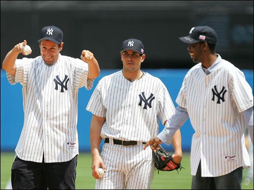 Adam Sandler, left, and Chris Rock, right, the stars of the new movie 'The Longest Yard,' throw out the first pitch at Yankee Stadium. Yankees starting pitcher Carl Pavano stands behind them.