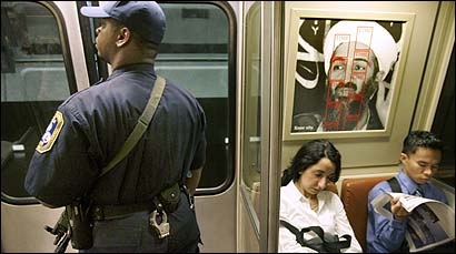Standing near a Time magazine poster featuring terrorist Osama bin Laden, a Metro Transit police officer, armed with a submachine gun, patrolled Washington's subway system.