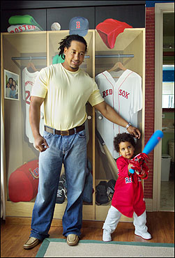 Manny Ramirez Sr. and Jr. take batting practice in front of the trompe l'oeil lockers that artist Jane O'Hara created.
