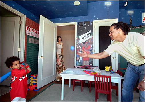 Manny Ramirez Jr. is ready to take a pitch from ''Papi'' as his mother, Juliana Ramirez, looks on. In the toddler's imaginatively decorated room, a life-size faux Fenway fan displays his support for the talented Red Sox outfielder.