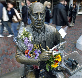 The Red Auerbach statue at Faneuil Hall, adorned with flowers on the day after his death.