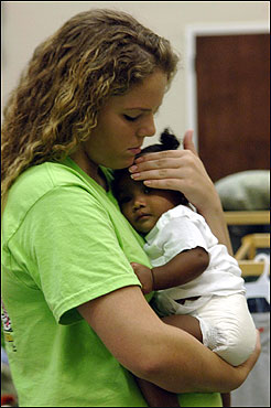 A shelter volunteer comforted a baby Thursday in Meridian, Miss. Workers, who feared a food shortage may occur by the end of the week, were told their 300 temporary residents could be there for up to four months.