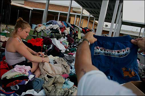Carrie Arceneaux and Eddie Hegler sorted through donated clothes Monday in Bay St. Louis, Miss. Charities across the nation are collecting donations to help with Hurricane Katrina relief efforts.