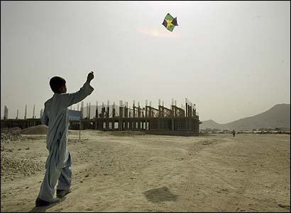 An Afghan boy flew a kite near a construction site for a market in Kabul last year. Reconstruction has progressed more slowly than expected.