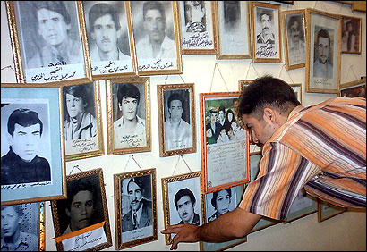 An Iraqi man adjusted the picture yesterday of a relative who was killed, allegedly by Saddam Hussein's regime, along with more than 140 others in the town of Dujail in 1982.