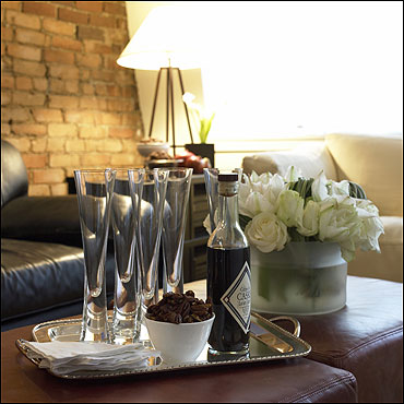 A leather ottoman that doubles as a coffee table holds a tray of champagne flutes.