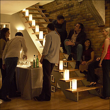 A focal point in the apartment, the staircase is a favorite perch for party guests. Here (from top), Justin Long, Haas, Tahiliani, and Laura Fitzgerald share the fun. At the bar, John Amend pours a drink for Fay as the host looks on.