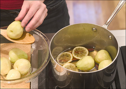3. Add the pears to the syrup, remove the lemon slices, and bring the syrup to a boil.