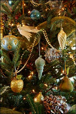 An up-close of the master bedroom tree shows Sliney's collection of ornaments that are augmented with dried hydrangea from her yard, brass beads, gold netting, and tiny white lights.