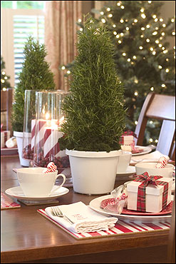 The table is decorated with rosemary trees, peppermint-striped candles, and Pettinelli & Bean place mats and napkins.