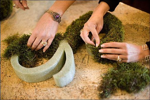 Wrap the moss around the letter, securing it with U-shaped florist's pins.