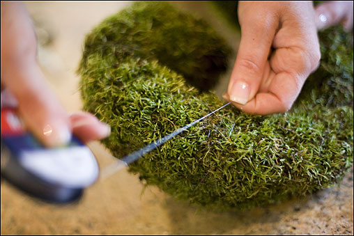 When the letter is completely covered, wrap it with monofilament to hold the moss in place. You can leave the moss loose or, for a more tailored look, trim it evenly with scissors. Add berries and a ribbon if you like, using the florist's pins.