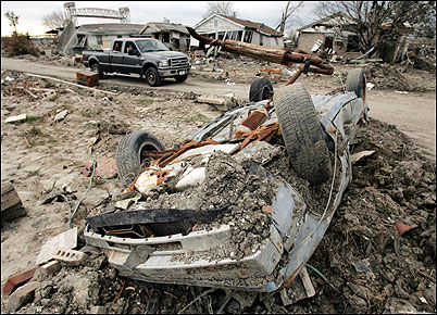 A car drove past destroyed homes and an overturned car as residents returned on a ''look and leave'' basis to the Lower Ninth Ward area yesterday in New Orleans.