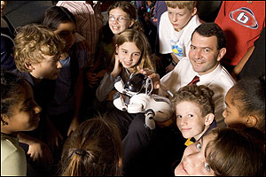 Can playing with a robotic puppy now prod youths (like these fifth-graders from the Advent School in Boston) to become engineers later? Museum of Science president Ioannis Miaoulis (right) thinks so.