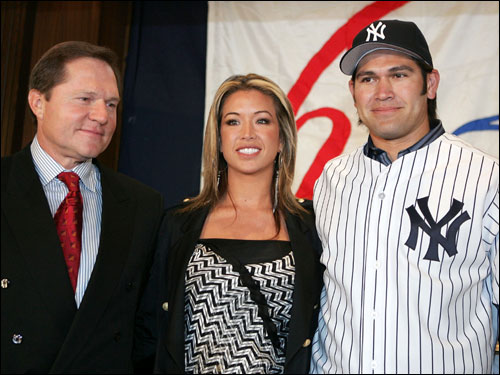Damon posed with his wife Michelle and agent Scott Boras after being introduced at Yankee Stadium.