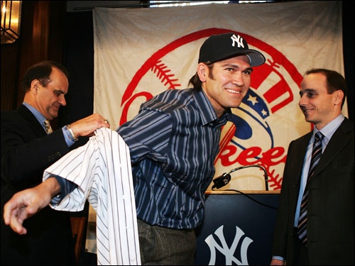 Damon tried on his uniform after being introduced as the new center fielder as manager Joe Torre (left) helped, and GM Brian Cashman looked on.