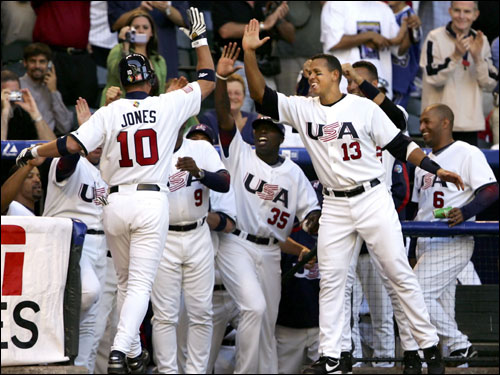 Chipper Jones (No. 10) of Team USA was congratulated by teammates Dontrelle Willis (No. 35) and Alex Rodriguez (No. 13) after hitting a solo home run against Team Mexico during the fourth inning of Round 1 Pool B game of the World Baseball Classic at Chase Field in Phoenix.