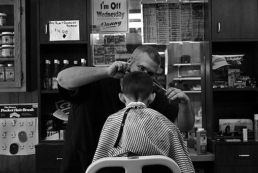 WEST ROXURY -- For a barber, no day is busier than Saturday. A sign in the front window at Phil's Barber Shop on Centre Street boasts 'seven and a half barbers' ready to clip, buzz, and comb every Saturday. On one recent Saturday, Danny Lourenco gave 8-year-old Patrick Dougherty a 'boy's regular.' After his trim, Patrick helped himself to three lollipops -- one for him and one for each of his sisters.There's been a barber shop at this spot on Centre Street for more than a century. Behind the coatrack in Phil's is a certificate issued in 1998 by the Boston Business Heritage Project that cites the shop for 100 years of 'enterprise, dedication, and long-time service to the community.' (Globe Staff Photo / Suzanne Kreiter) audio: Click the play button below to hear Danny's brother Dana discussing the shop and his life as a barber <object classid='clsid:02BF25D5-8C17-4B23-BC80-D3488ABDDC6B' width='200' height='30' codebase= 'http://www.apple.com/qtactivex/qtplugin.cab'> (Audio by Scott LaPierre, Boston.com)