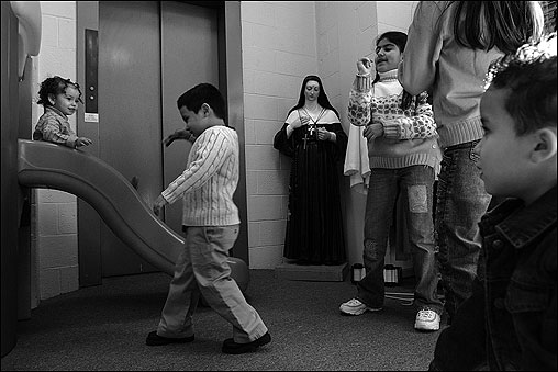 EAST BOSTON -- While their parents attend Mass at the Madonna Queen Shrine, children amuse themselves in the next-door play room. A statue of St. Rita of Cascia, patron of impossible causes, stands in a corner. The shrine, situated on the highest point in East Boston, was established in 1954 with the dedication a 35-foot copper and bronze statue of the madonna that overlooks Boston Harbor. Masses at the shrine, which is run by the priests of Sons of Divine Providence, are said in four languages -- English, Spanish, Italian, and Brazilian-Portuguese. The priestly order was founded by St. Luigi Orione, whose motto was 'Do good to all, help everybody, harm nobody.' (Globe Staff Photo / Suzanne Kreiter) audio: Click the play button below to hear sacristan Carol Bellinska discussing the Spanish-language mass <object classid='clsid:02BF25D5-8C17-4B23-BC80-D3488ABDDC6B' width='200' height='30' codebase= 'http://www.apple.com/qtactivex/qtplugin.cab'> (Audio by Scott LaPierre, Boston.com)