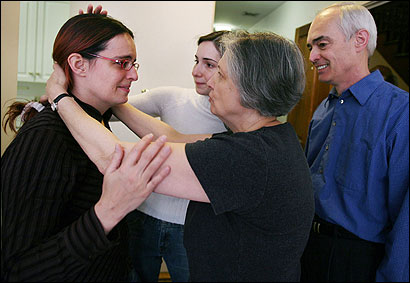 Former captive Jill Carroll (left) had a joyous reunion with her mother, Mary Beth, her twin sister, Katie, and her father, Jim, in Boston yesterday. Carroll was set free in Iraq last week after 82 days as a hostage.